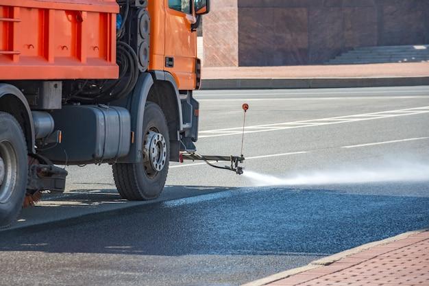Maszyna Do Czyszczenia Myje Asfaltową Nawierzchnię Ulicy Miasta. Premium Zdjęcia