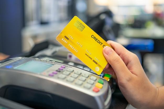 Maszyna machnięcia kartą kredytową i młoda osoba posiadająca kartę kredytową, aby zapłacić za zakupy Premium Zdjęcia