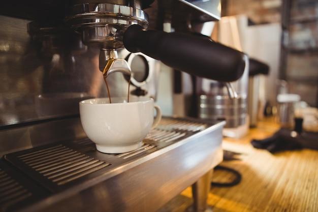 Maszyna robi filiżance kawy w kawiarni Premium Zdjęcia