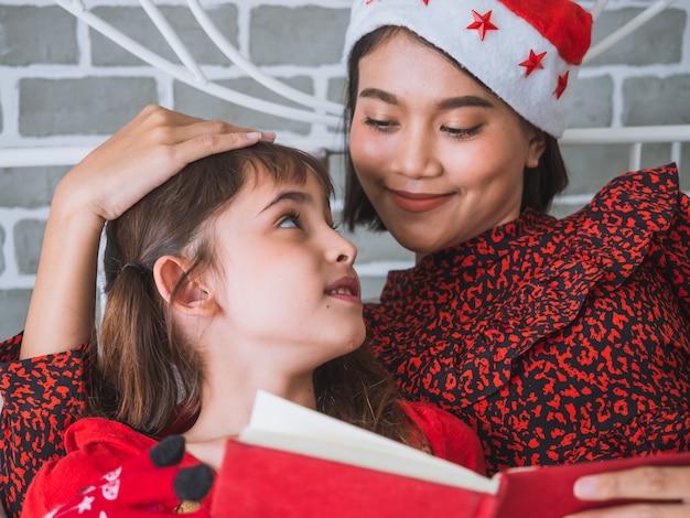 Matka czyta książkę jej córka w dzień bożego narodzenia, szczęśliwy rodzinny pojęcie Premium Zdjęcia