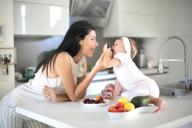 Matka Daje Jedzenie Swojemu Dziecku W Kuchni Premium Zdjęcia