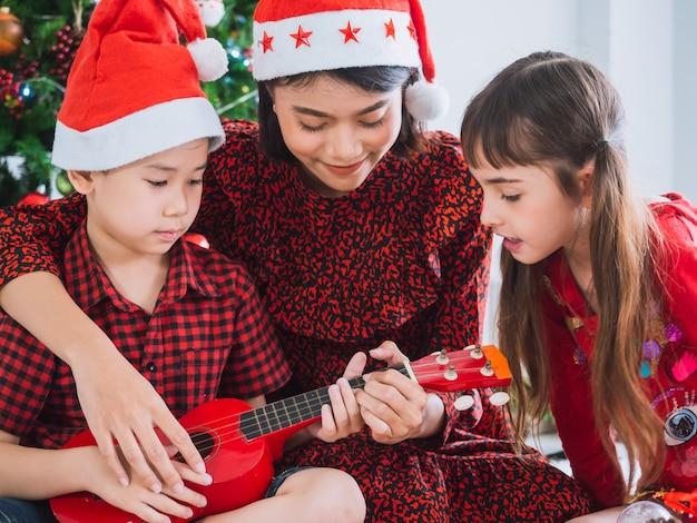 Matka grała na gitarze w boże narodzenie z chłopcem i dziewczynką Premium Zdjęcia