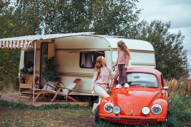 Matka I Córeczka Relaksujący I Zabawy Na Wsi Na Wakacje W Samochodzie Kempingowym Z Czerwonym Samochodem Retro Premium Zdjęcia