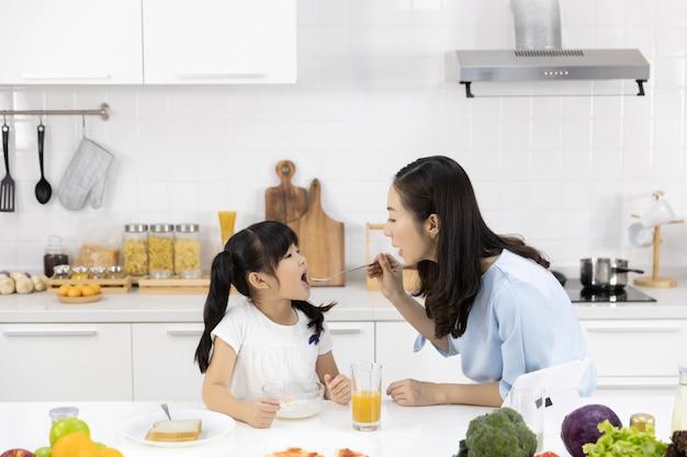 Matka I Córka Jedzą śniadanie I Oglądają Media Na Tablecie Premium Zdjęcia