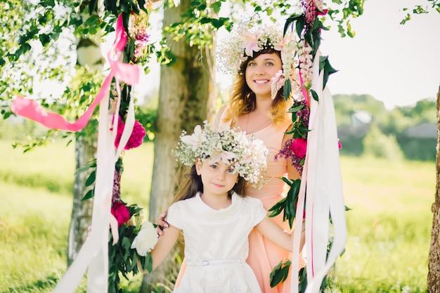 Matka i córka na huśtawki w słoneczny letni dzień Premium Zdjęcia
