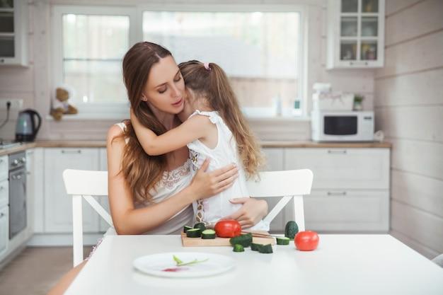 Matka i córka przytulanie w kuchni Premium Zdjęcia