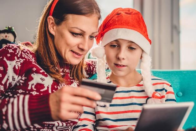 Matka i córka robi zakupy online w domu podczas bożych narodzeń Premium Zdjęcia