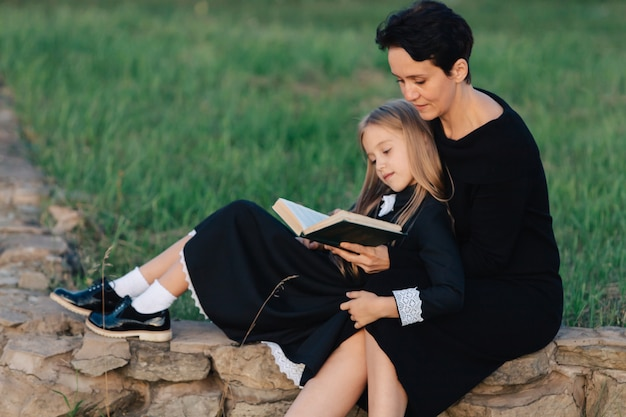 Matka I Córka Siedzą Na Kamiennej ławce I Czytają Książkę. Kobieta Z Dzieckiem W Czarne Sukienki. Premium Zdjęcia