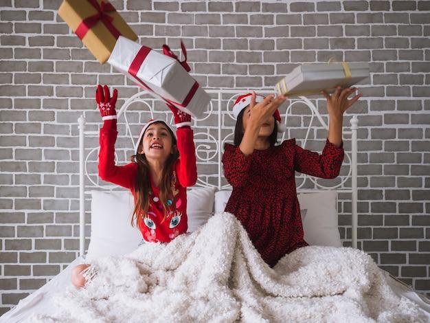 Matka i córka świętują boże narodzenie, rzucając pudełko w powietrze Premium Zdjęcia