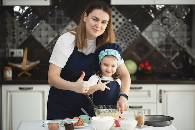 Matka I Córka W Identycznych Fartuchach I Czapkach Szefa Kuchni Gotują W Kuchni Premium Zdjęcia