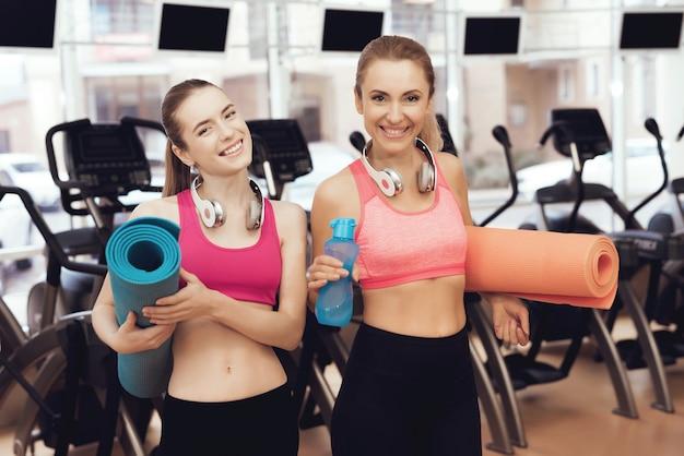 Matka i córka w sportswear z matami stoi przy gym Premium Zdjęcia
