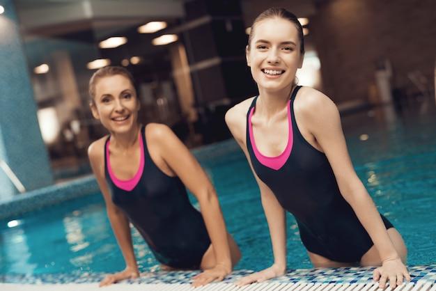 Matka i córka w strojach kąpielowych na granicy basenu w siłowni Premium Zdjęcia