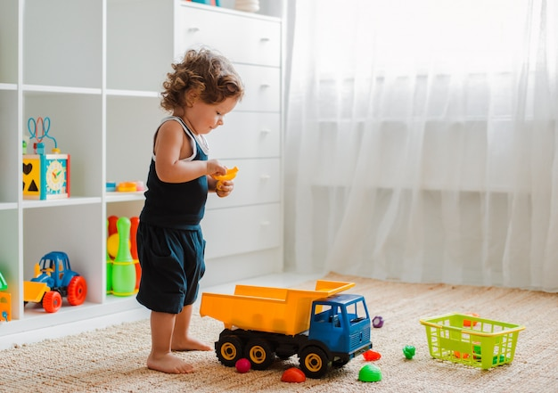 Matka i dziecko bawią się na podłodze w pokoju dziecinnym. mama i mały chłopiec robią z plastikowymi kolorowymi zabawkami. Premium Zdjęcia