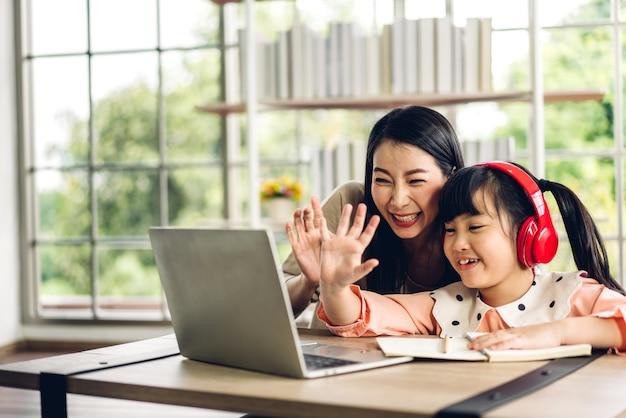 Matka I Dziecko Z Azji Mała Dziewczynka Uczy Się I Patrzy Na Komputer Robiąc Pracę Domową Studiując Wiedzę Z Systemem E-learningu Edukacji Online Premium Zdjęcia