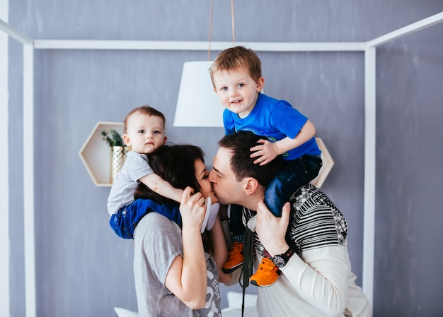 Matka I Ojciec Całują Się I Trzymają Na Ramionach Swoich Synów Darmowe Zdjęcia