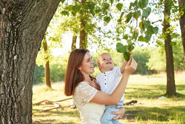 Matka i syn chodzić w parku w lecie o zachodzie słońca Premium Zdjęcia