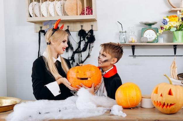 Matka i syn trzyma dyni podczas przygotowań do halloween. Premium Zdjęcia