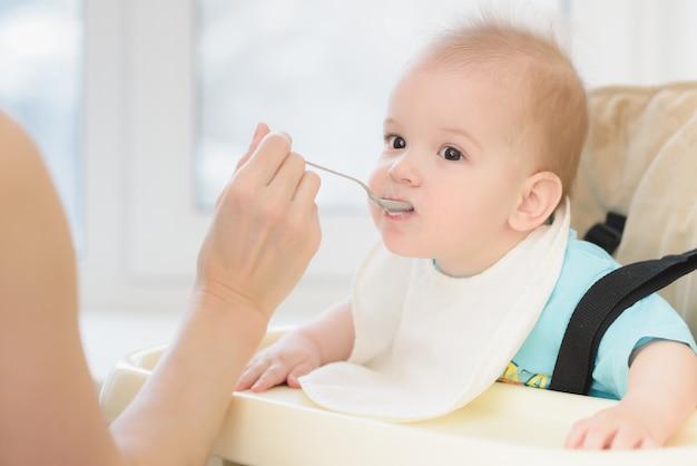 Matka karmi swoje dziecko owsianka dzień Premium Zdjęcia