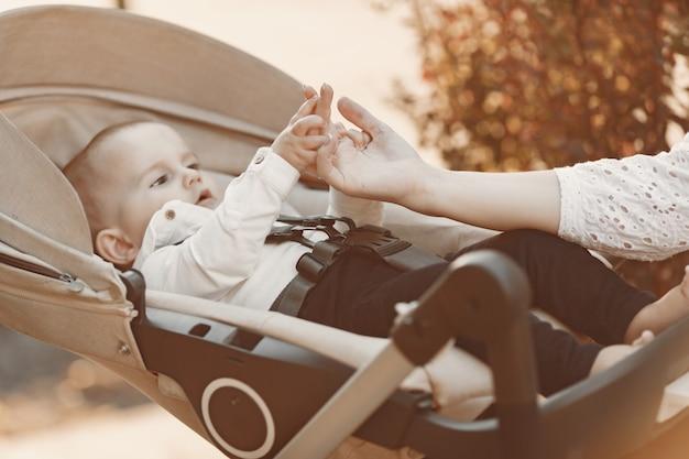 Matka Nosi Maskę Na Twarz. Kobieta Siedząca Na ławce. Mama Z Wózkiem Dziecięcym Podczas Pandemii Na Spacerze Na świeżym Powietrzu. Darmowe Zdjęcia