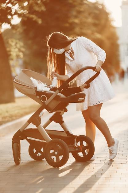 Matka Nosi Maskę Na Twarz. Kobieta Spaceru Dziecko W Wózku. Mama Z Wózkiem Dziecięcym Podczas Pandemii Na Spacerze Na świeżym Powietrzu Darmowe Zdjęcia
