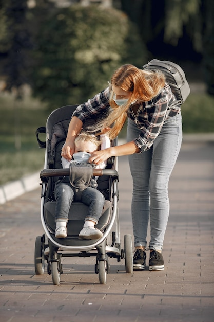 Matka Nosi Maskę Na Twarz. Mama Z Wózkiem Dziecięcym Podczas Pandemii Na Spacerze Na świeżym Powietrzu. Darmowe Zdjęcia