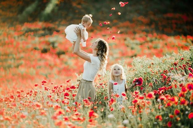 Matka trzyma dziecko na wysokości, a starsza córka uśmiecha się na polu makowym Darmowe Zdjęcia