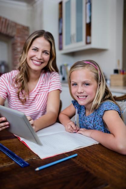 Matka używa cyfrową pastylkę podczas gdy pomagający córki z jej pracą domową Premium Zdjęcia