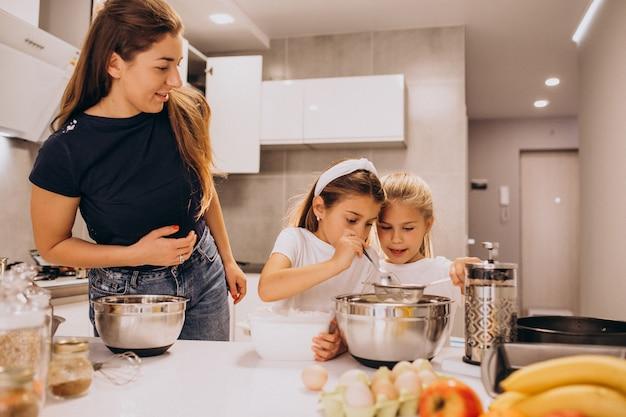 Matka z dwiema córkami w kuchni do pieczenia Darmowe Zdjęcia