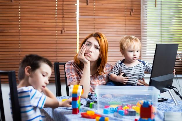 Matka Z Dwoma Małymi Chłopcami Na Kolanach Próbuje Się śmiać W Domu. Młoda Kobieta Opiekuje Się Dziećmi I Pracuje Na Komputerze. Premium Zdjęcia
