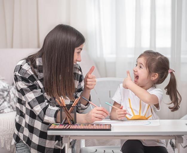 Matka Z Dzieckiem Siedzi Przy Stole I Odrabia Lekcje. Dziecko Uczy Się W Domu. Nauka W Domu. Miejsce Na Tekst. Darmowe Zdjęcia