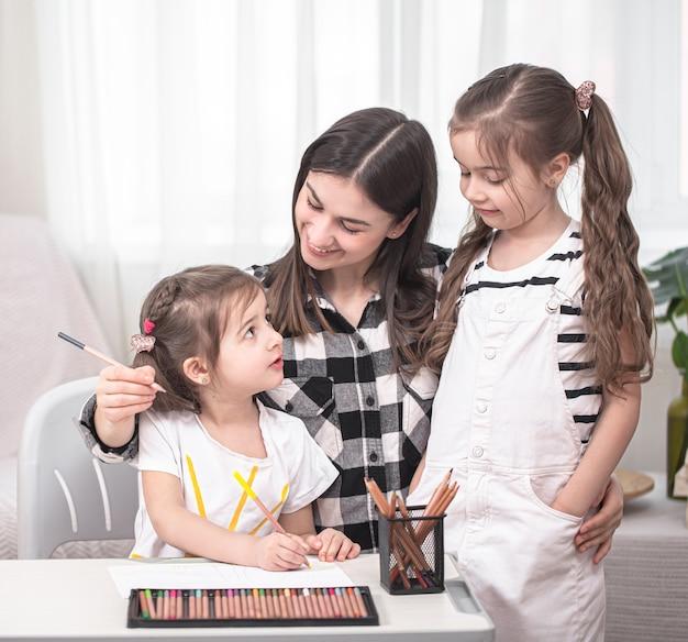 Matka Z Dziećmi Siedzi Przy Stole I Odrabia Lekcje. Dziecko Uczy Się W Domu. Nauka W Domu. Miejsce Na Tekst. Darmowe Zdjęcia