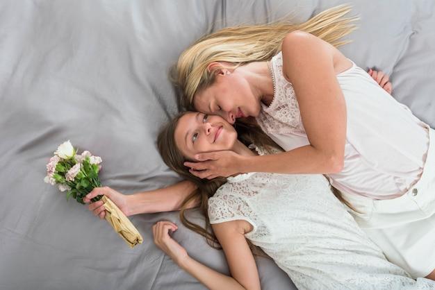 Matka Z Kwiatami ściska Córkę Na łóżku Darmowe Zdjęcia