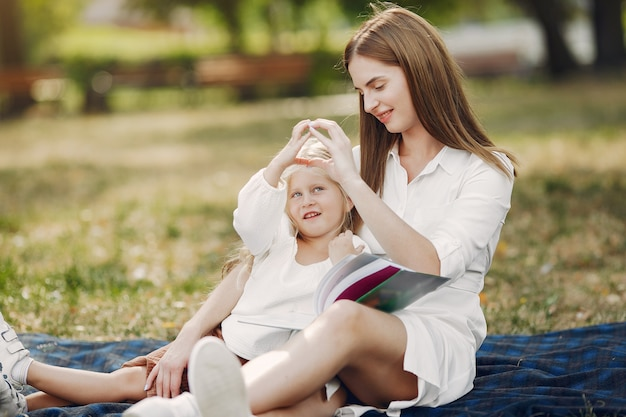 Matka z małą córeczką siedzącą na kratce i czytająca książkę Darmowe Zdjęcia