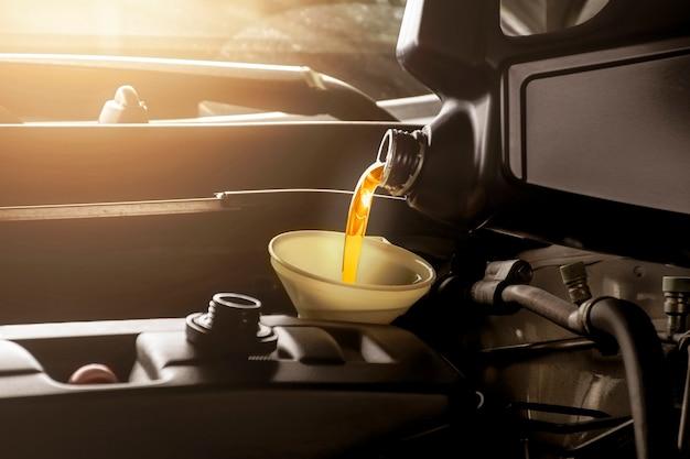 Mechanik Mężczyzna Wlewający Olej Silnikowy Do Silnika Samochodu Premium Zdjęcia