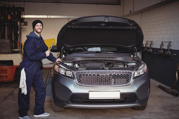 Mechanik, Uśmiechając Się I Trzymając Narzędzie Klucza W Garażu Darmowe Zdjęcia