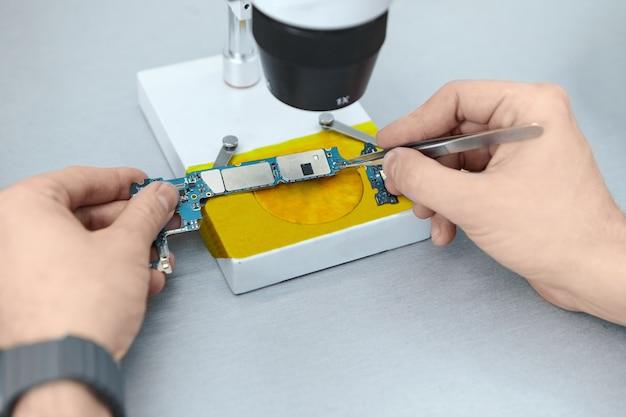 Mechanik Używa Pincety Do Przytrzymywania Elementów Elektronicznych Płytki Drukowanej Podczas Naprawy Telefonu Komórkowego Pod Mikroskopem Darmowe Zdjęcia