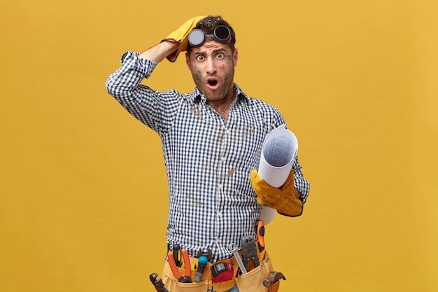 Mechanik W Kraciastej Koszuli, Rękawiczkach, Okularach Ochronnych, Trzymający Zwinięty Papier O Brudnej Twarzy Z Pracy Patrzący Dużymi Oczami I Otwartymi Ustami Po Zrobieniu Czegoś Złego Darmowe Zdjęcia