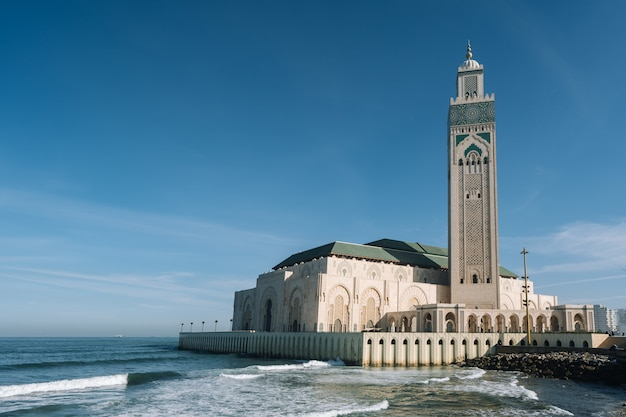 Meczet Hassana Ii Otoczony Wodą I Budynkami Pod Błękitnym Niebem I światłem Słonecznym Darmowe Zdjęcia