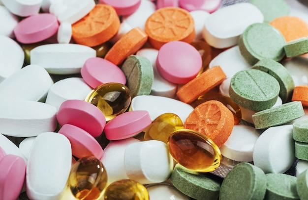 Medyczne kolorowe pigułki, kapsułki lub suplementy do leczenia i opieki zdrowotnej na jasnym tle Premium Zdjęcia