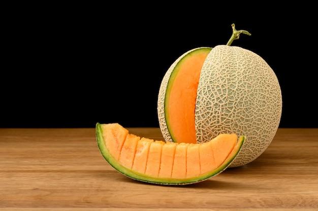 Melonowa Owoc Pokrajać Na Drewnianym Stole Z Czarnym Tłem Premium Zdjęcia