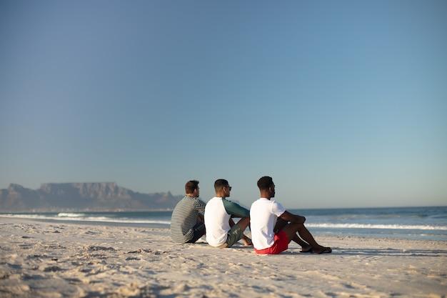 Męscy przyjaciele relaksuje wpólnie na plaży Darmowe Zdjęcia