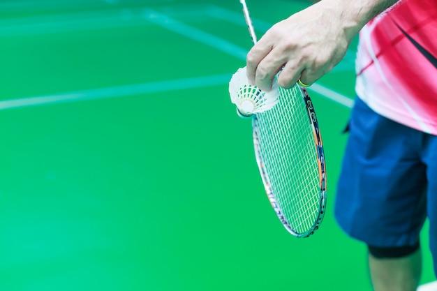 Męska badminton pojedyncza gracz ręka trzyma białego wahadłowa koguta wraz z kantem Premium Zdjęcia