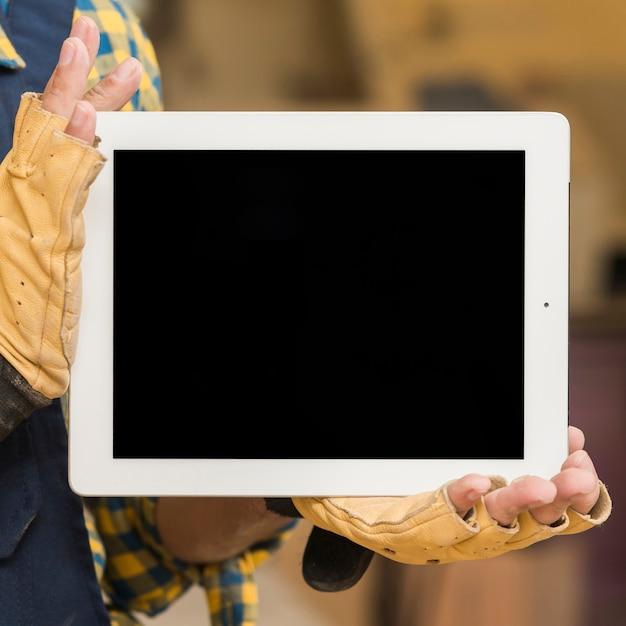 Męska cieśla ręka z ochronnymi rękawiczkami pokazuje pustego ekranu cyfrową pastylkę Darmowe Zdjęcia