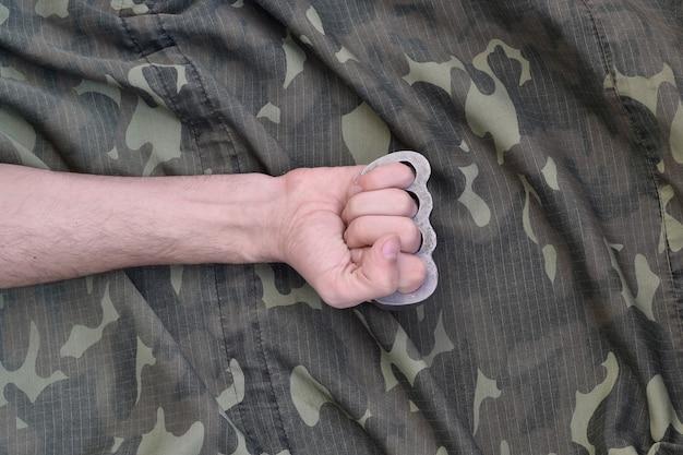 Męska Pięść Z Mosiężnymi Kostkami Na Tle Kamuflażu. Pojęcie Kultury Skinheadów, Ręcznie Robiona Broń Biała Premium Zdjęcia