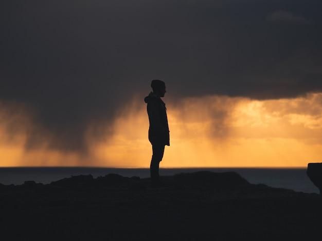 Męska Pozycja Na Falezie Z żółtym I Chmurnym Niebem W Tle Darmowe Zdjęcia