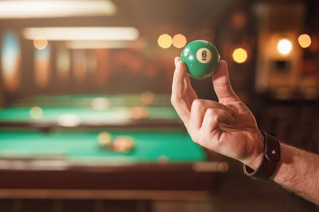 Męska Ręka Pokazuje Bilardową Kulę Numer Osiem. Premium Zdjęcia