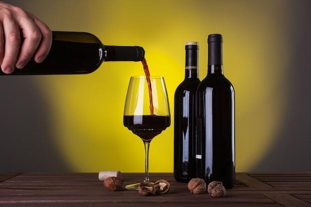 Męska Ręka Trzyma Butelkę Czerwonego Wina I Wlewając Do Kieliszka Premium Zdjęcia