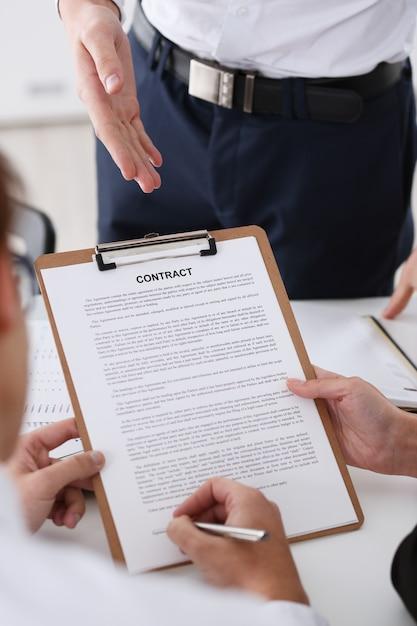 Męska Ręka W Koszulowej Oferty Kontrakta Formie Na Schowka Ochraniaczu I Srebnym Piórze Podpisywać Zbliżenie. Znajdź Okazję Dla Zysku Motywem Urzędnika Decyzja Związek Sprzedaż Korporacyjna Agent Ubezpieczeniowy Koncepcja Premium Zdjęcia
