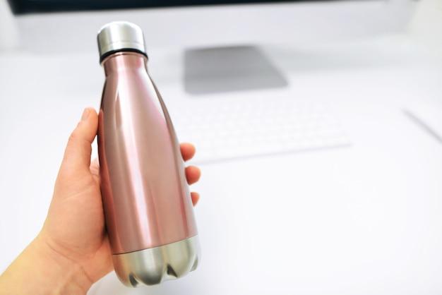 Męska Ręka Wyjmuje Z Biurka Stalową Butelkę Termiczną Eco Na Wodę. Metalowa Butelka Na Wodę. Premium Zdjęcia