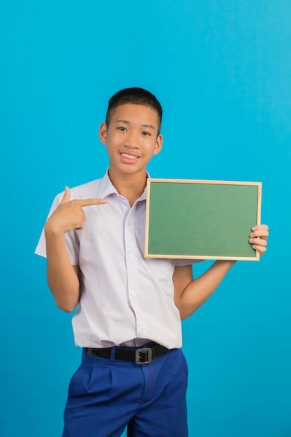 Męski azjatycki student z gestem rąk podniesionych i wskazanych zieloną tablicą trzymającą drugą rękę na niebiesko. Darmowe Zdjęcia